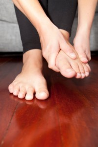 A woman rubs her aching feet on the sofa