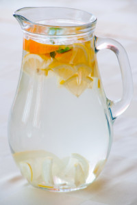 Jug of cold water with lemon and orange slices