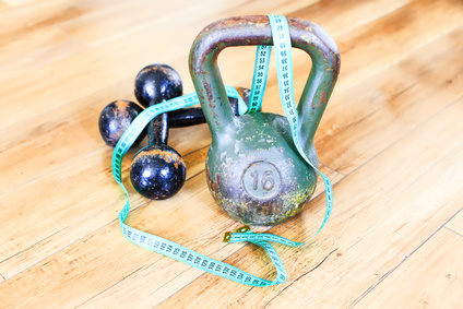 strength training. weight and dumbbells belted measuring tape symbolize a way of gaining a beautiful and healthy body