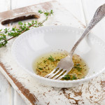 Dressing with thyme in a white bowl. Selective focus