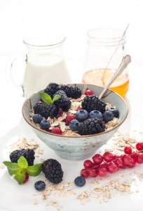 Healthy breakfast with granola and fresh berries on white