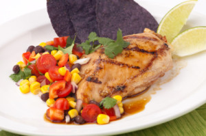 Grilled chicken breast with salsa - black beans, corn, tomatoes, chilli pepper, cilantro, red onion - with  blue corn tortilla chips.