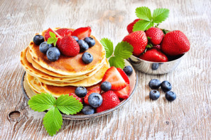 Stack of pancakes with fresh strawberries, blueberries, maple syrup and honey for breakfast, selective focus
