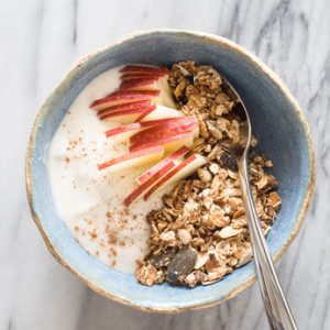 A Bowl of Homemade  Granola with Apple Slices, Plain Iogurt and Cinnamon