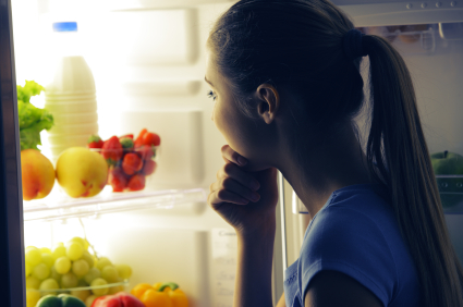 Young woman craving food choosing near refrigerator at night