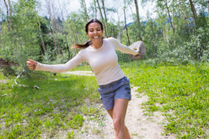 Hispanic woman skipping in forest